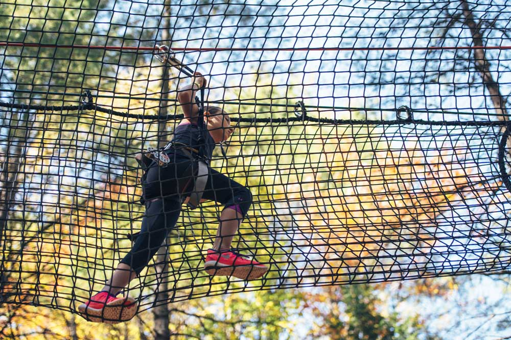 girl climbing through net fencing