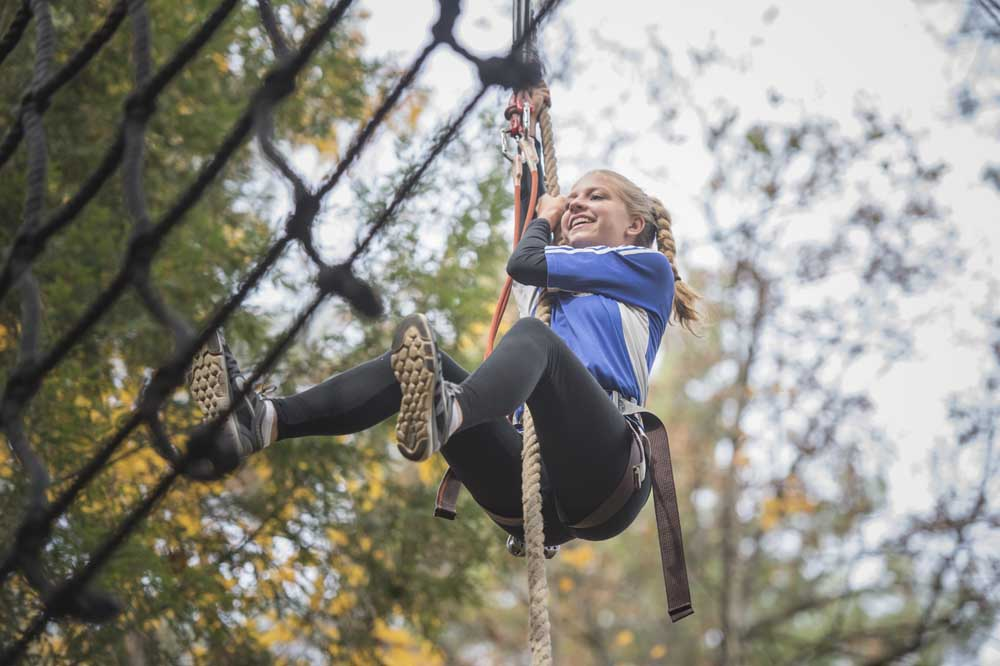 girl laughing swinging on zip line