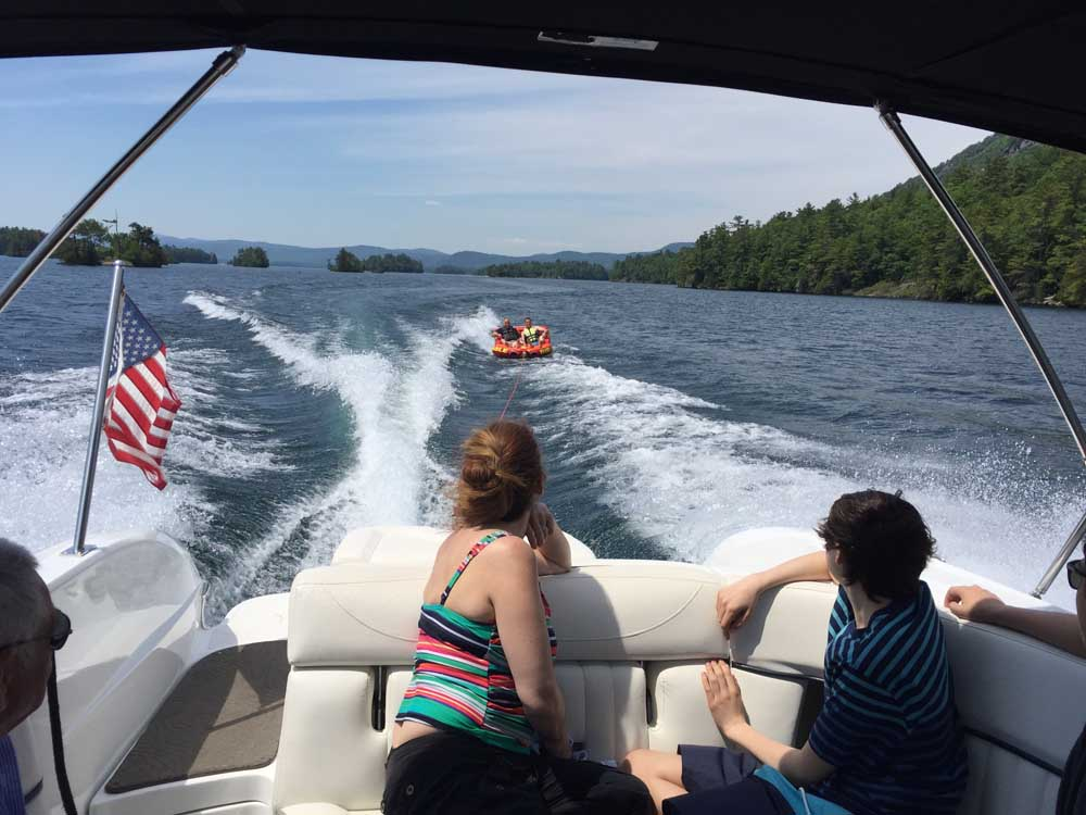 two people on boat watching friends tubing