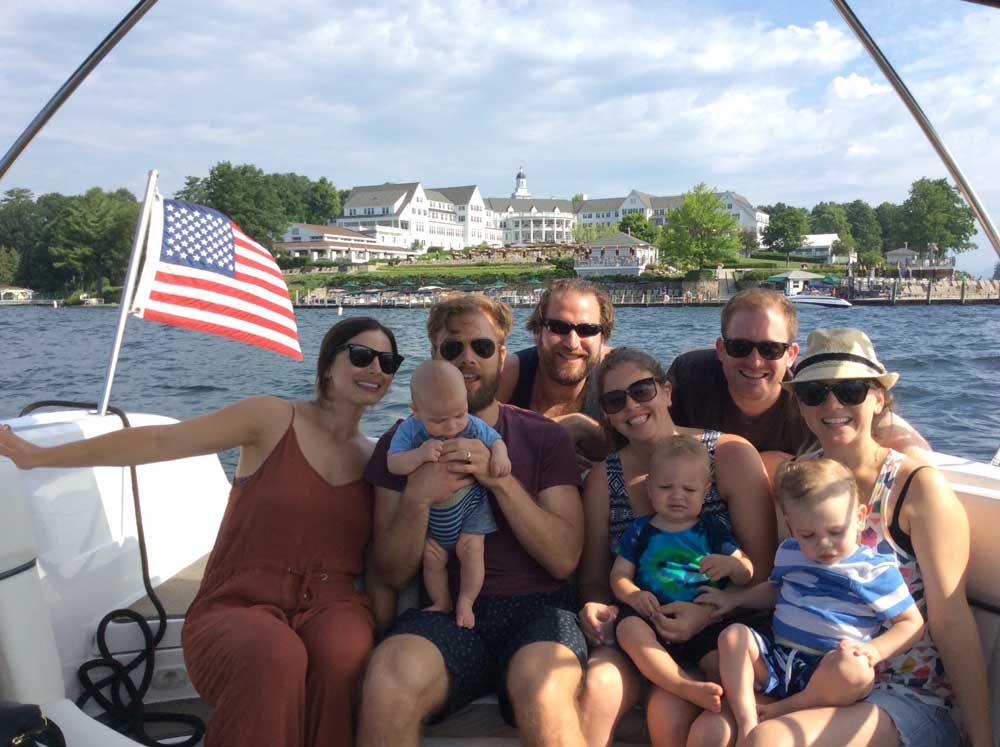 friends and family smiling for group photo on boat