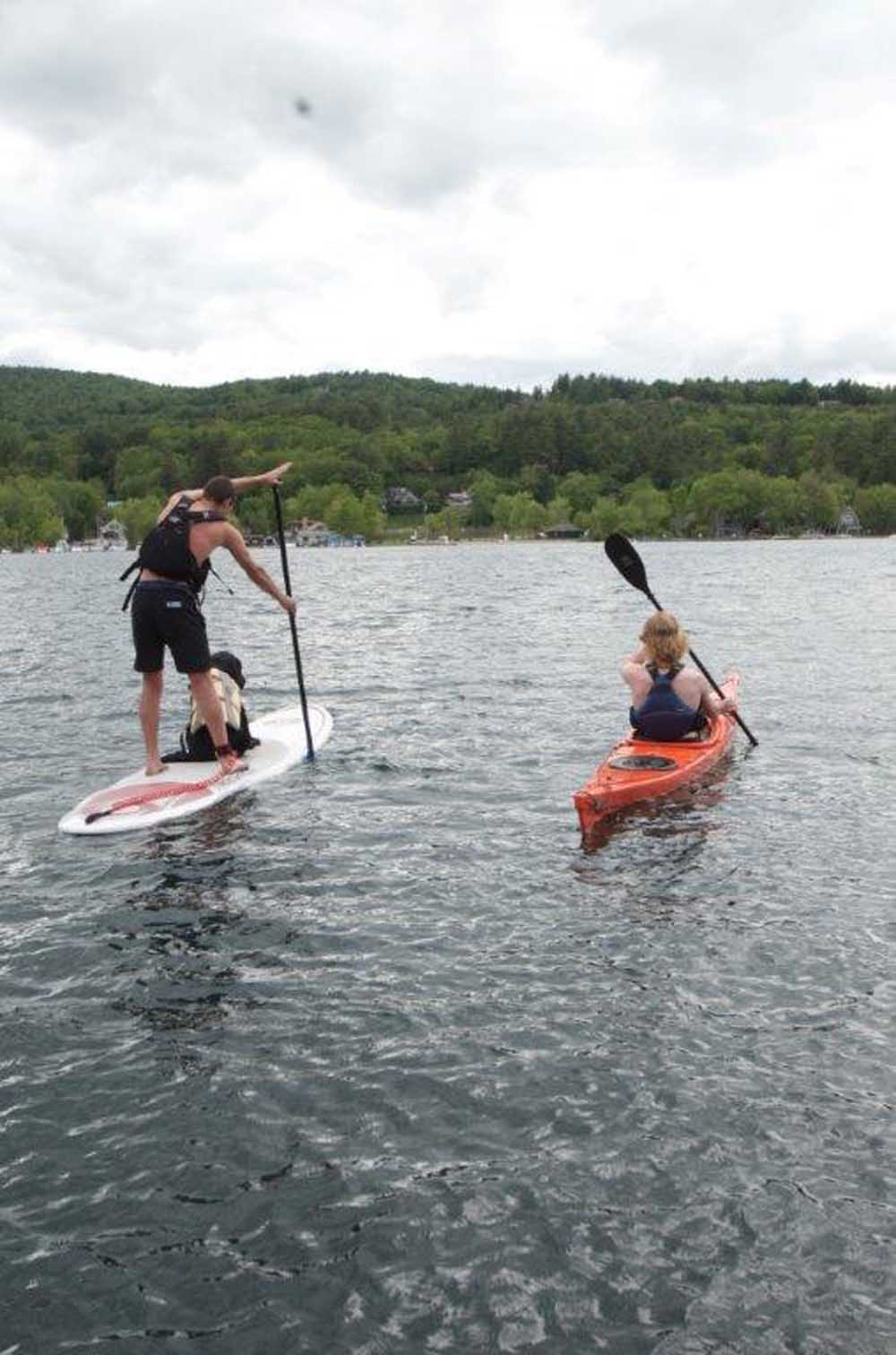 man on stand up paddle board with another man in kayak