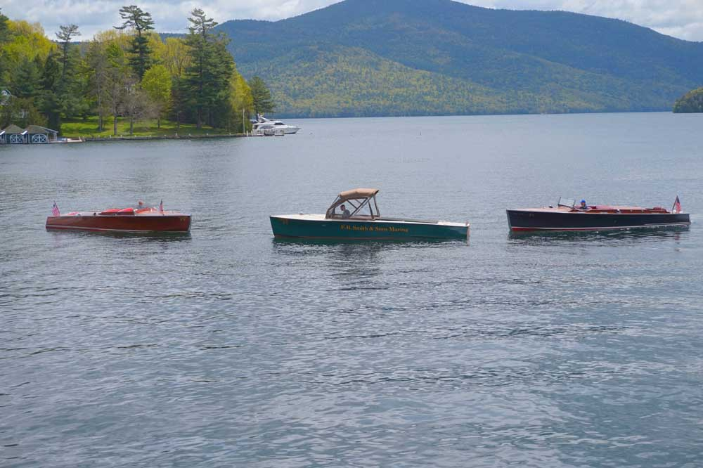 three boats on water with adirondacks in background