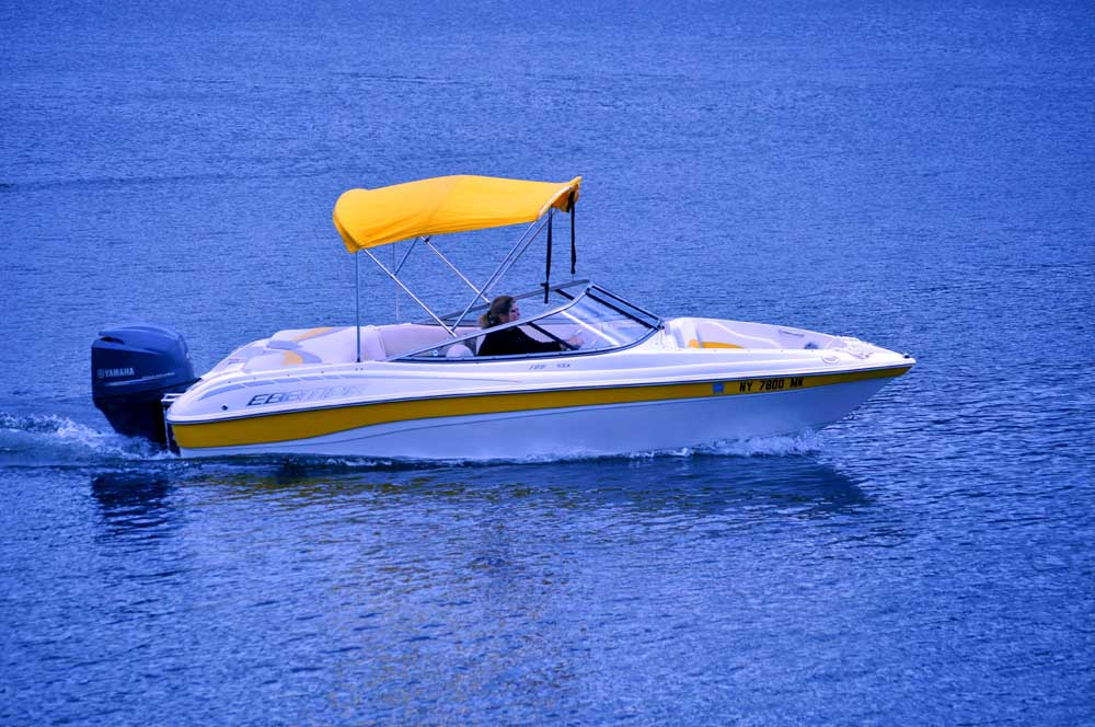 white and yellow boat on bright blue water