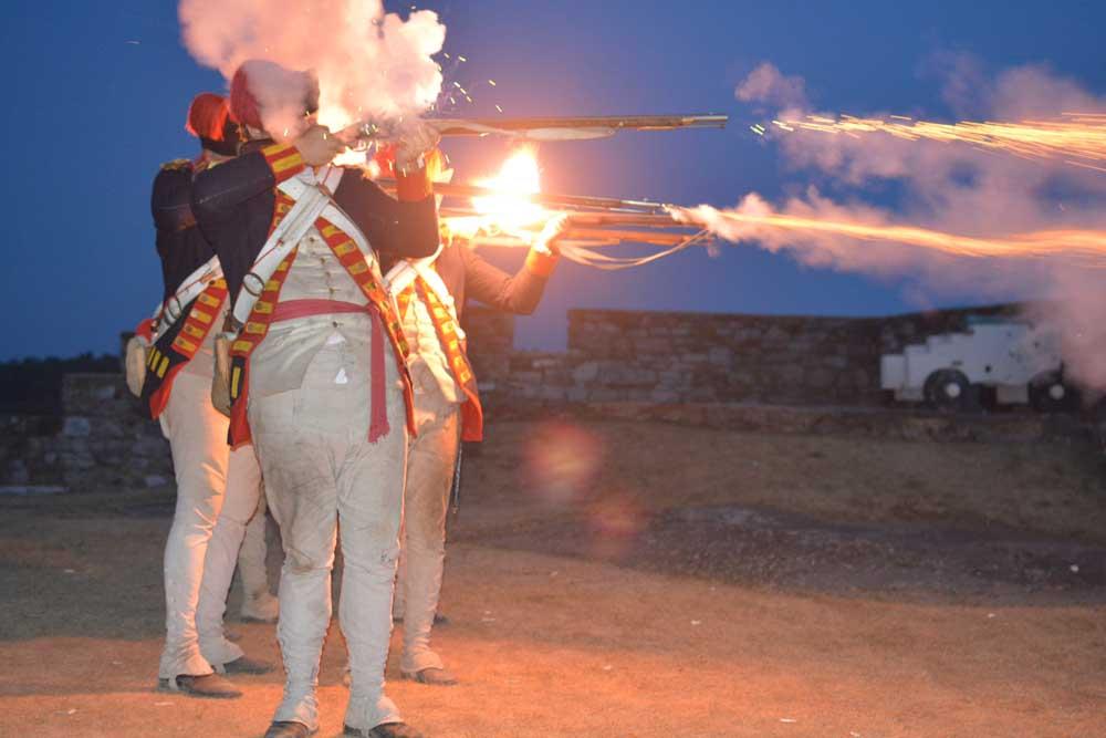 men dressed as civil war army members mid musket shot