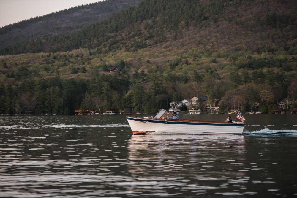 boat coasting across lake george in fall