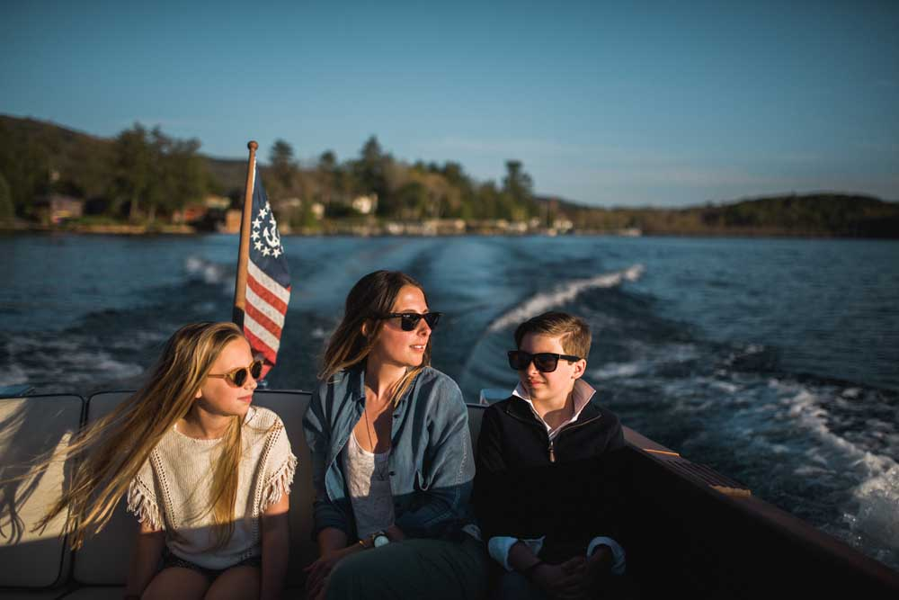 family sitting on back of boat