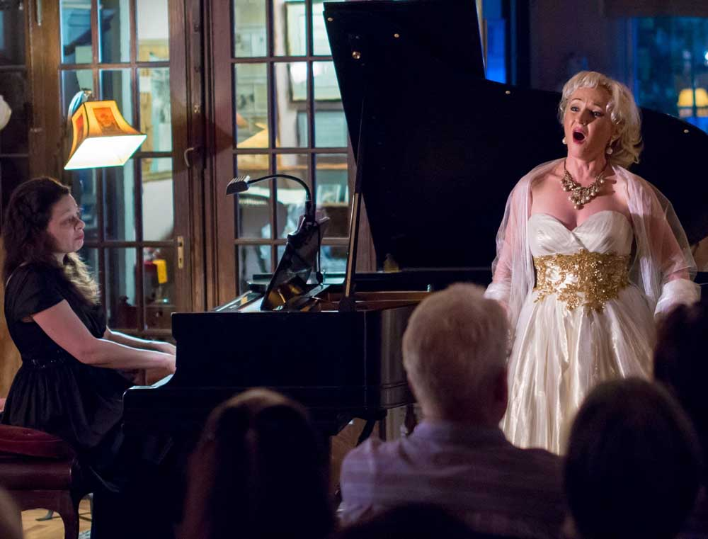 woman singing in white dress to crowd while woman plays piano