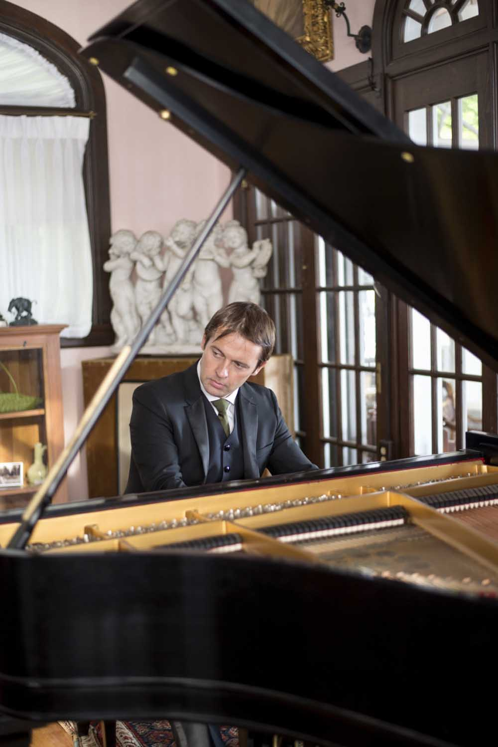 man in suit playing grand piano