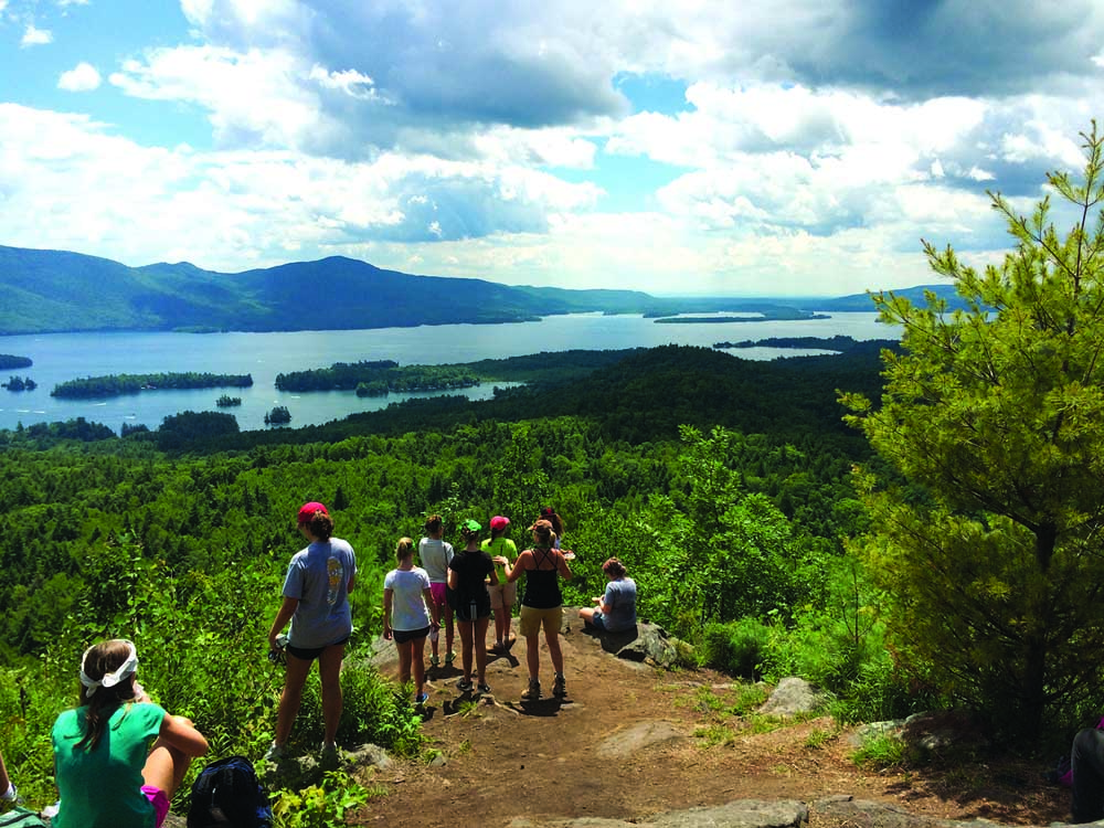 group on mountaintop looking at lake george and adirondacks