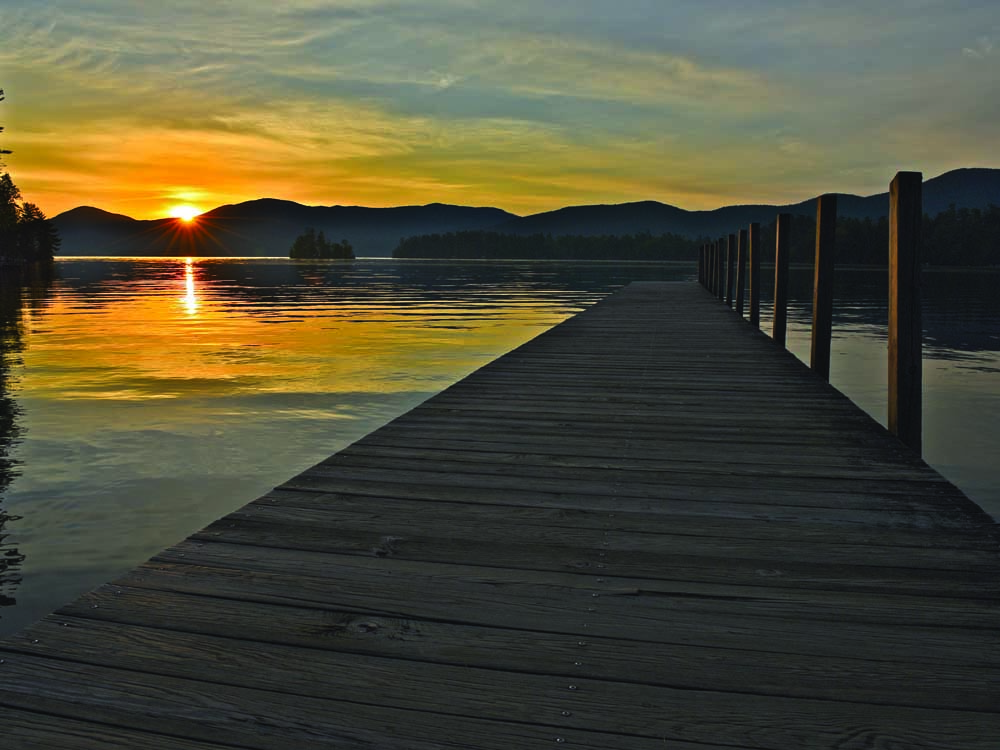 wood dock with sun setting over mountain
