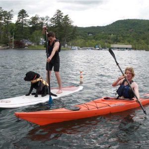 two men and a dog on kayak and stand up paddleboard